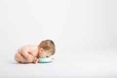 O bebê inclina a cara no bolo de aniversário Foto de Stock