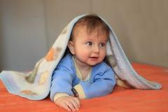 O bebê louro coberto por uma cobertura foto de stock