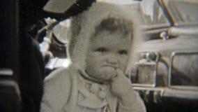 1937: O bebê mal-humorado põe o dedo na boca e olha divertido video estoque