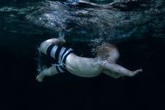 O bebê mergulha sob a água foto de stock royalty free