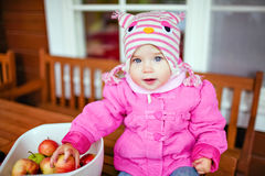O bebê muito bonito em um revestimento cor-de-rosa mantém as maçãs no outono Foto de Stock