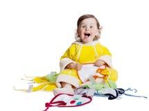 O bebê no macaquinho amarelo escolhe o babador, isolado no branco fotografia de stock royalty free