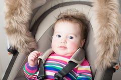 O bebê no rosa fez malha o vestido que senta-se no carrinho de criança Fotografia de Stock