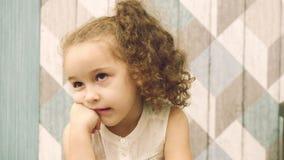 O bebê olha pensativamente de lado, olhando lateralmente com seus olhos Criança, crianças, emoções filme