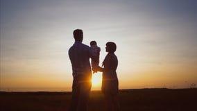 O bebê, o paizinho e a mamã felizes da família estão jogando sobre nos raios da noite bonita do verão do por do sol no parque filme