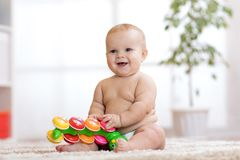 O bebê pequeno adorável no tecido senta-se no tapete e nos jogos com brinquedo em casa Profundidade de campo rasa Fotografia de Stock Royalty Free