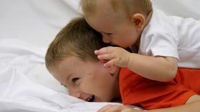 O bebê pequeno bonito joga com seu irmão mais grande, crianças tem muito divertimento em casa vídeos de arquivo