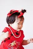 O bebê pequeno chinês feliz no cheongsam vermelho tem o divertimento Foto de Stock Royalty Free