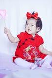 O bebê pequeno chinês feliz no cheongsam vermelho tem o divertimento Fotografia de Stock Royalty Free