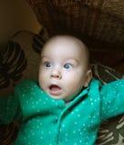 O bebê pequeno com os olhos abertos e surpreendido no verde veste-se espantar-se Fotos de Stock Royalty Free