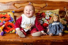 O bebê pequeno com uma cauda senta-se em um sofá com descansos e os brinquedos bordados fotos de stock royalty free