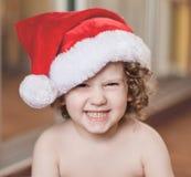 O bebê pequeno em um tampão vermelho imagem de stock