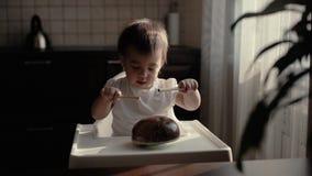 O bebê pequeno golpeia um lápis em um instrumento musical Kalimba e em risos filme