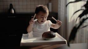 O bebê pequeno golpeia um lápis em um instrumento musical Kalimba no movimento lento filme