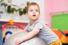 O bebê pequeno joga com um fitball no gym Fotos de Stock Royalty Free