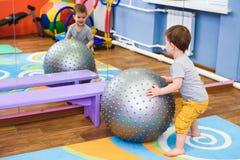 O bebê pequeno joga com um fitball no gym Imagem de Stock Royalty Free