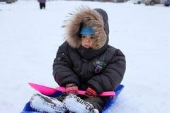 O bebê pequeno na roupa morna que senta-se em um trenó no inverno nos olhares severos da neve congela-se para não querer andar imagem de stock royalty free