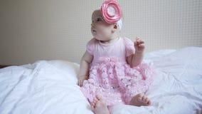 O bebê pequeno no vestido cor-de-rosa está sentando-se na cama no quarto video estoque