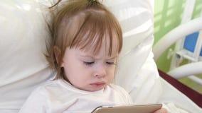 O bebê pequeno olha os desenhos animados que jogam no telefone na facilidade médica na cama de hospital Criança da recuperação na vídeos de arquivo