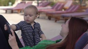 O bebê pequeno pressiona a tela do smartphone, sentando-se perto da mãe filme