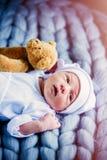 O bebê pequeno que veste um branco veste-se e chapéu com urso taddy imagem de stock royalty free