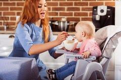 O bebê pequeno senta-se na cadeira alta e em alimentar com colher sua mãe bonita Imagem de Stock Royalty Free