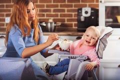 O bebê pequeno senta-se na cadeira alta e em alimentar com colher sua mãe bonita Fotografia de Stock