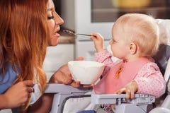 O bebê pequeno senta-se na cadeira alta e em alimentar com colher sua mãe bonita Fotografia de Stock Royalty Free