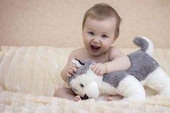 O bebê pequeno senta-se na cama com cão de brinquedo fotos de stock