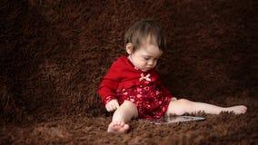 O bebê que guarda uma tabuleta e senta-se no assoalho vídeos de arquivo
