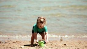 O bebê que jogam a cubeta e a pá escavam na areia video estoque