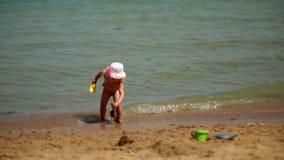 O bebê que jogam a cubeta e a pá escavam na areia vídeos de arquivo