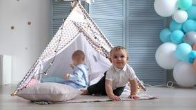 O bebê rasteja longe da outra criança, mas retorna-lhe na barraca das crianças filme
