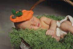 O bebê recém-nascido bonito está dormindo em um chapéu em uma cesta Sono do bebê Fotografia de Stock Royalty Free