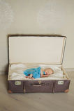O bebê recém-nascido bonito está dormindo em um vertical da mala de viagem Imagens de Stock