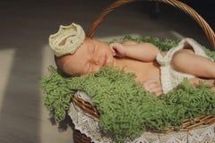 O bebê recém-nascido bonito está dormindo em uma coroa em uma cesta Imagem de Stock
