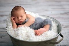 O bebê recém-nascido, dormindo pacificamente na cesta, vestiu-se na malha fotografia de stock