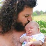 O bebê recém-nascido está dormindo em sua mão do pai Imagem de Stock