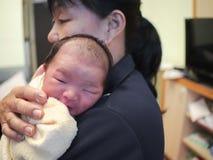 O bebê recém-nascido está sendo guardado com mãe foto de stock