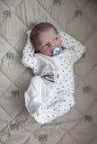 O bebê recém-nascido pensativo está colocando nos dorminhocos brancos com bocal azul Fotografia de Stock