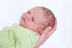 O bebê recém-nascido pequeno em seus pais entrega olhar de sobrancelhas franzidas fotos de stock royalty free