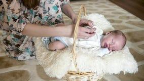O bebê recém-nascido que encontra-se em uma cesta, mamã veste o fato-macaco recém-nascido vídeos de arquivo