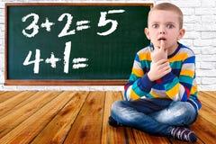O bebê resolve exemplos da matemática O estudante pensa e sente perto da placa Tarefas matemáticas imagens de stock royalty free