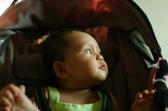O bebê senta-se em seu olhar do carrinho de criança deixado Foto de Stock Royalty Free