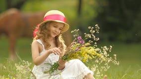 O bebê senta-se em um esclarecimento, vira-se as flores selvagens rasgadas e faz-se um ramalhete delas Movimento lento vídeos de arquivo