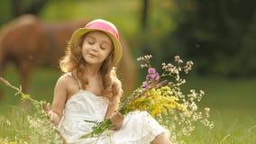 O bebê senta-se em uma clareira em um sarafan e o chapéu, guarda flores selvagens e sorrisos Movimento lento filme