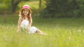O bebê senta-se em uma clareira em um sarafan e o chapéu, guarda flores selvagens e sorrisos Movimento lento vídeos de arquivo