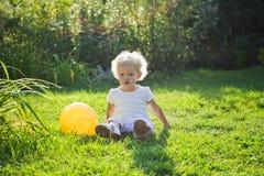 O bebê senta-se em uma grama fotografia de stock royalty free