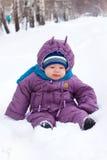 O bebê senta-se na neve Fotografia de Stock Royalty Free