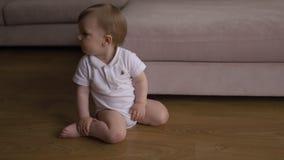 O beb? senta-se no assoalho em sua casa da casa familiar que sente horizontalmente sonolento e curiosa - a crian?a veste o polo b filme